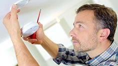 Man installing fire detector