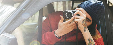 Man hanging out car window taking a picture with a camera