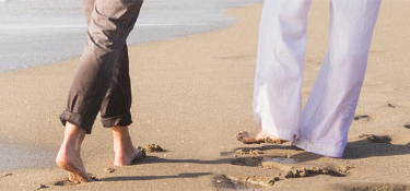 Retired couple walking along the beach