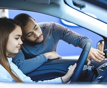 Un hombre y una mujer mirando un carro