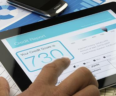 Persona utilizando una tableta para ver un informe crediticio