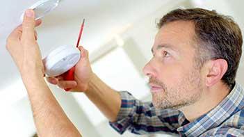 man replacing smoke alarm