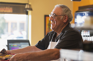 Man behind counter smiling at customer