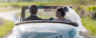 Couple in wedding attire driving into sunset in car with Just Married sign on it.