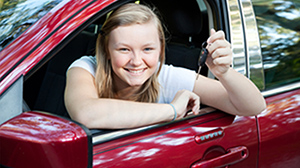 Teenage girl sitting in the drivers seat of a red car holding up her car keys