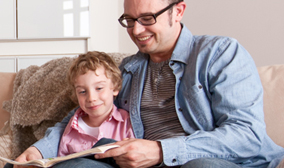Man reading to a child on the couch