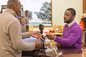 Man helping a customer at the register
