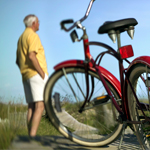 Older man looking at view while standing next to a bike