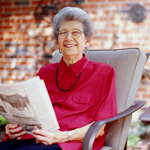 Older women smiling while reading paper