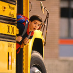 Young boy looking our school bus door
