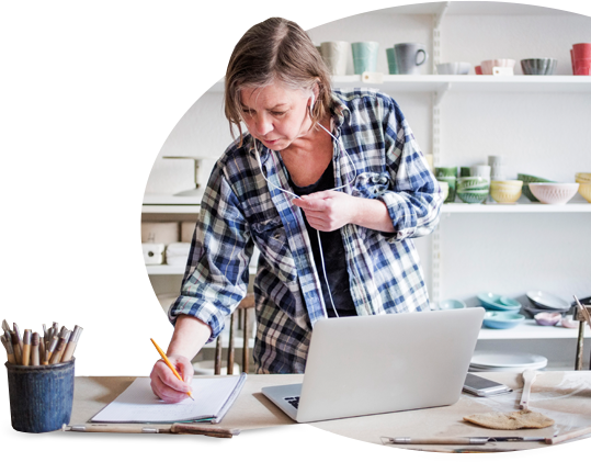 Woman in flannel shirt stands in front of a desk. She has her laptop open and is taking notes.