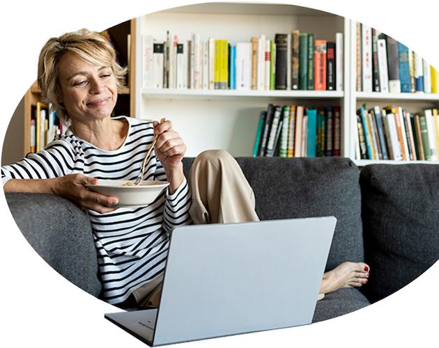 Una mujer habla con su agente a través de su computadora portátil mientras desayuna y se relaja.