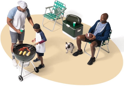 View from above of a father and son grilling hotdogs and corn on the cob as a neighbor and his dog supervise from a nearby lawn chair.