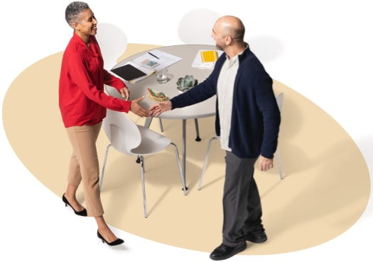 State Farm agent stands to greet male customer.