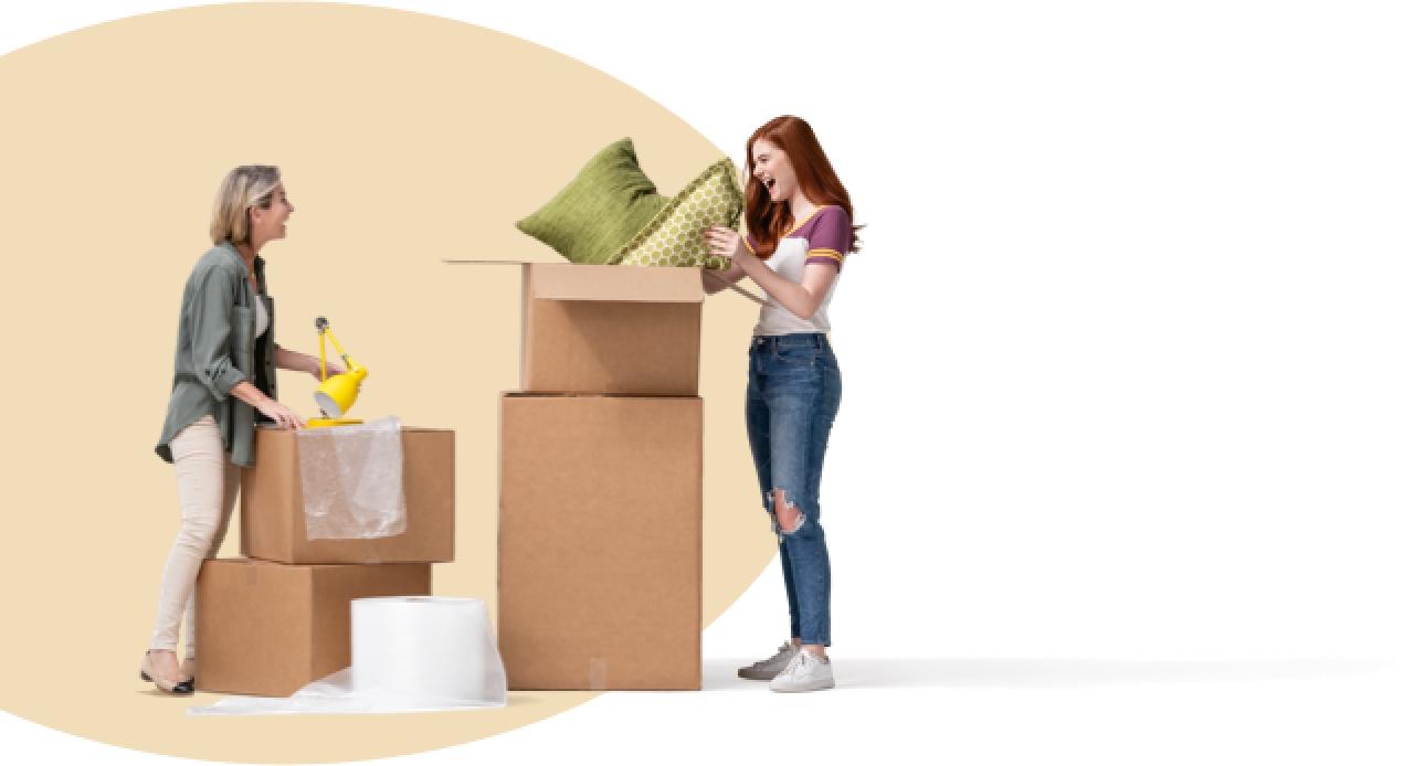 Al mudarse a su nuevo apartamento, una hija sonríe al empacar cojines verdes en cajas. Su sonriente madre sostiene una lámpara de escritorio amarilla.