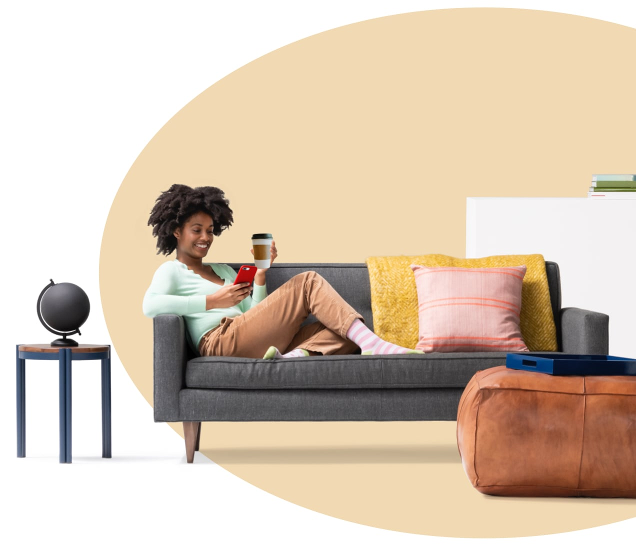 Woman sitting on couch holding a glass of water while reading her iPhone about what renters insurance covers. A globe sits on side table.