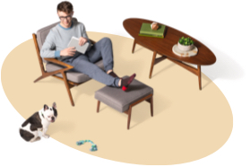 Man in grey sweater and slacks relaxes in chair with his tablet. His foot rests on an ottoman. His Boston terrier ignores him.