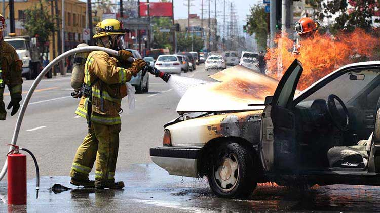 Fireman spraying water under the hood of a car on fire.