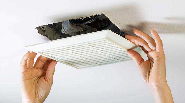 Two hands installing ceiling vent.