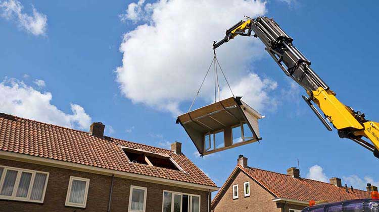 A section of a prefab home lowered into place by crane