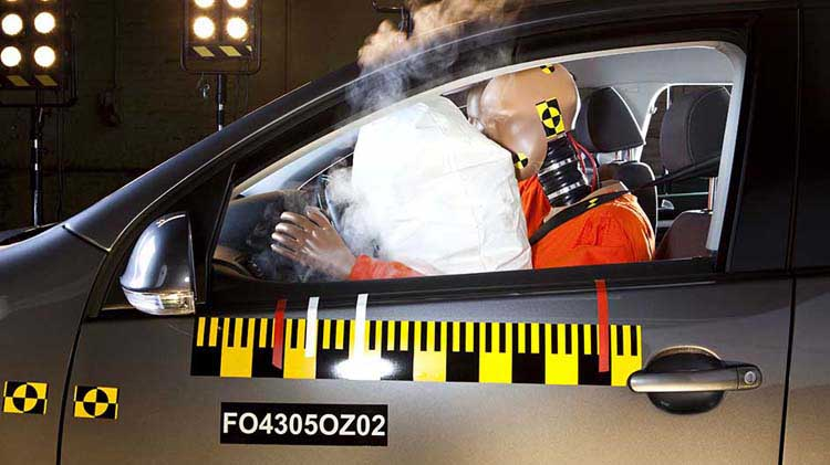 Crash test dummy in driver seat with deployed airbag