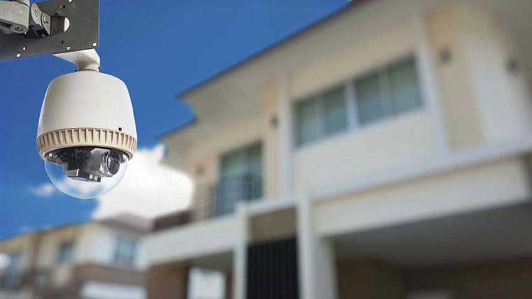 A remote home monitoring camera is attached to the outside of a building.