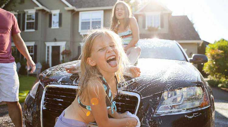 A family is washing their recently refinanced car at home.