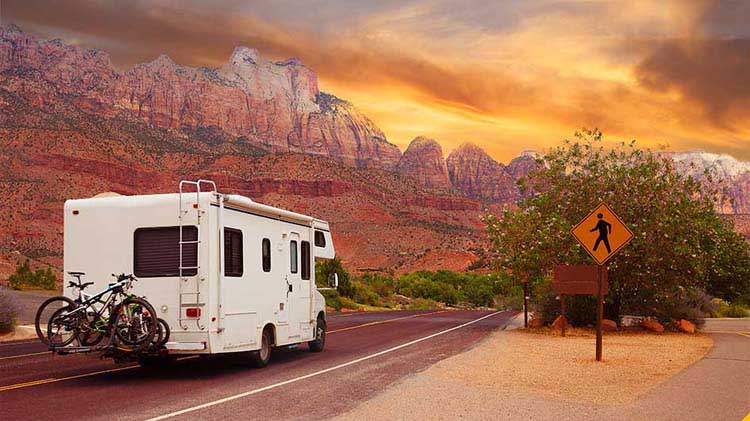 RV on the road with mountains and sunset