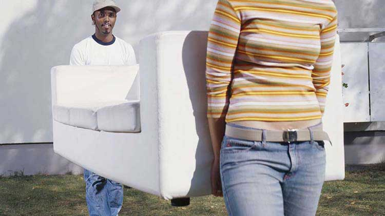 Two people carrying a couch after getting moving insurance.