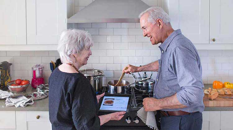 Mature couple discusses their retirement while looking at information on a tablet device.