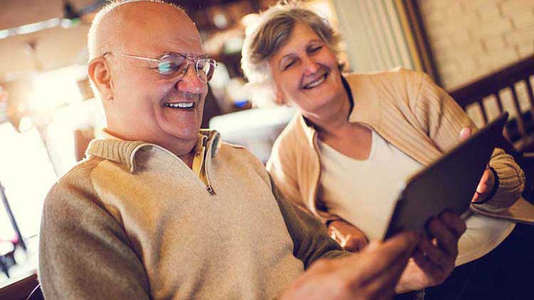 Older couple looks at information on a tablet device.