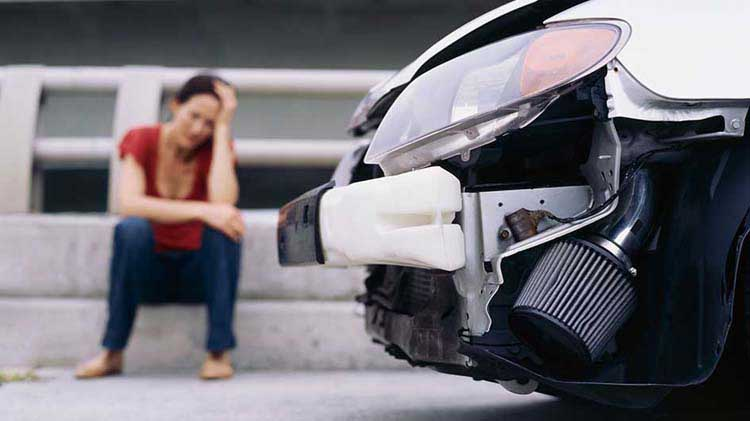 Upset woman near her car after an accident