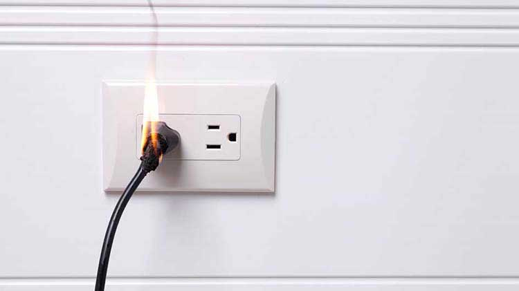 Electric cord in an outlet lighting on fire
