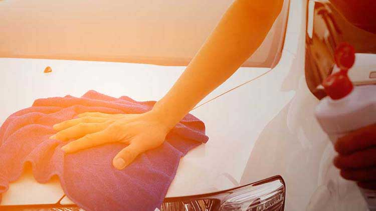 Hand resting on towel on car hood