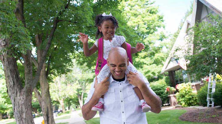 A man carries his daughter on his shoulder while thinking about saving for college