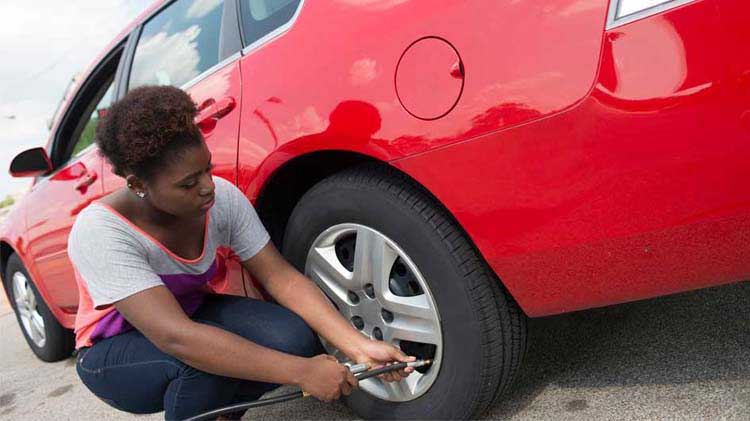 A woman working on her car's tire
