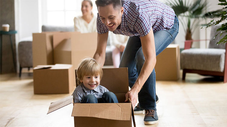 Father pushing son across the floor in cardboard box with mother and other moving boxes behind them.