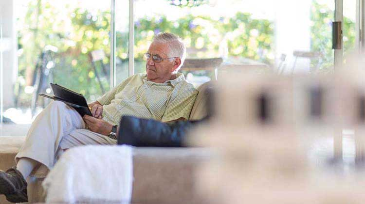 An elderly man on his couch researching Medicare online.