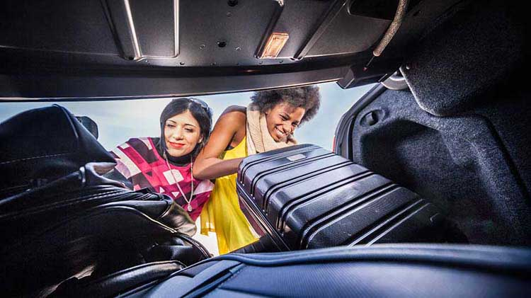Women putting suitcases into car trunk