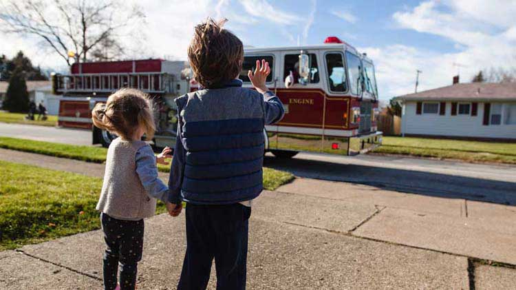 Kids waving at a fire truck