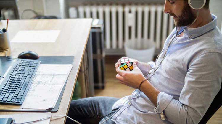 Man at a workstation working on a Rubik's Cube