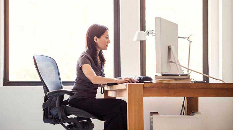 Woman sitting at desk typing