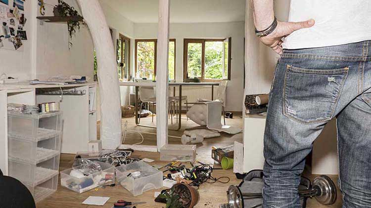 Man surveys interior of ransacked home.
