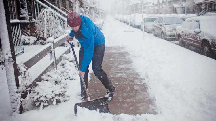 Man shovels snow with knees bent