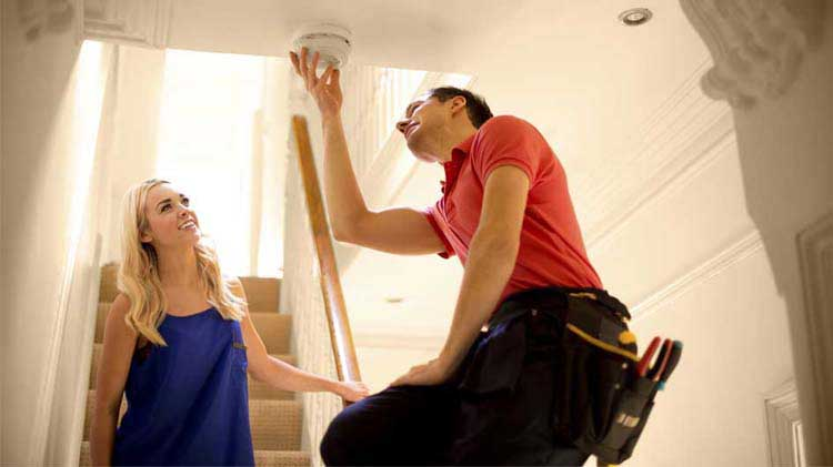 Woman watching man install a smoke detector