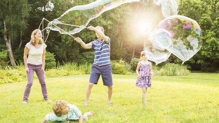 Family playing with giant soap bubbles in a yard
