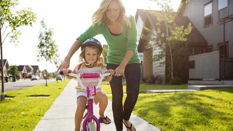 Mom helping young daughter learn to ride her bike