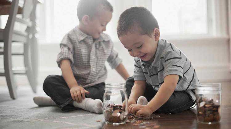 Two little boys are sitting on the floor protecting their finances by placing the coins in jars.