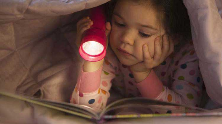 Little girl reading under a blanket with a flashlight