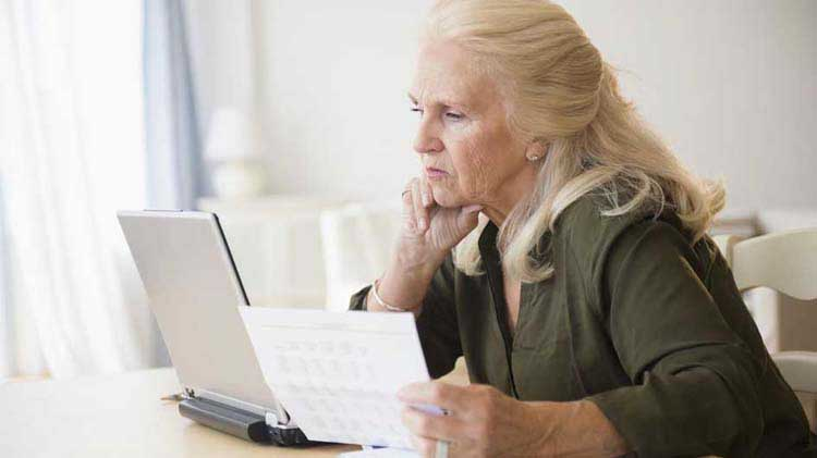 Older woman looking at a laptop and paperwork